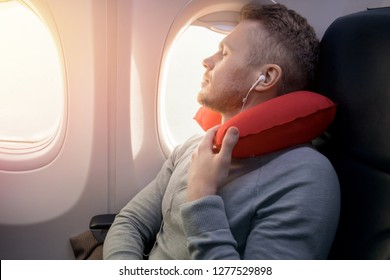 Male passenger of airplane listens to music and enjoys pillow for sleeping in chair. Concept travel
