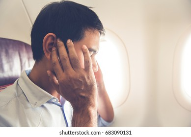 Male passenger having ear pop on the airplane while taking off (or landing)