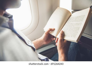 Male passenger killing time by reading book while traveling on the plane