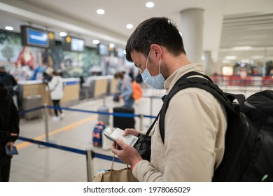 Male passenger in mask with backpack uses smartphone and stands with social distance on check-in line at airport of Cyprus, paphos city. Travel by plane during quarantine coronavirus, new norm.