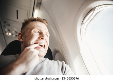 Male passenger in plane screams and cries, aerophobia. background of porthole. Concept fear of flying on airplane.