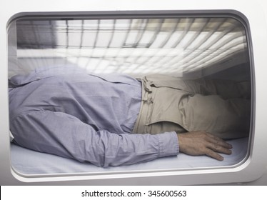 Male patient aged 45-55 wearing blue shirt and beige chino trousers lying down in hyperbaric oxygen chamber receiving Hyperbaric Oxygen Therapy (HBOT)