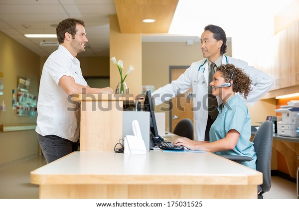 Male patient with doctor and nurse at reception desk in hospital