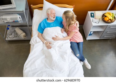 male patient hospital bed and girl sitting near