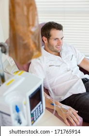 Male patient with IV drip attached to his hand during chemotherapy in hospital room