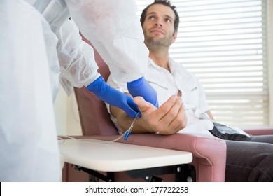 Male patient looking at nurse while receiving intravenous treatment in hospital room