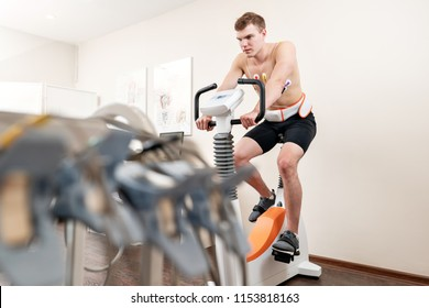 A male patient, pedaling on a bicycle ergometer stress test system for the function of his heart checked. Athlete does a cardiac stress test in a medical study, monitored by the doctor.