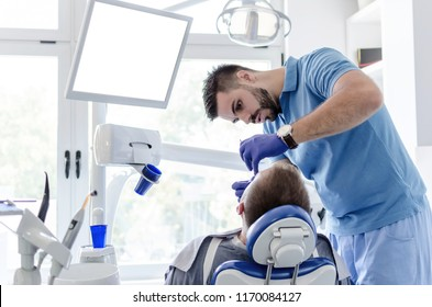 Male patient receiving anesthesia from male dentist in stomatology office.