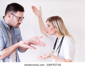 Male patient rejecting to take spoon full of pills from angry female doctor