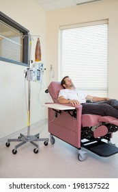Male patient relaxing on chair during chemotherapy in hospital room