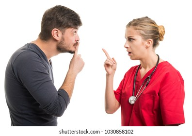 Male patient showing silence gesture to female doctor isolated on white background