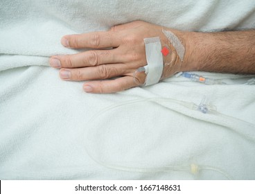Male Patient Sleeps on the Bed in hospital with intravenous normal saline.