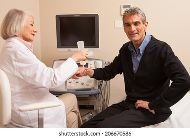 Male patient undergoing wrist ultrasound with female doctor.