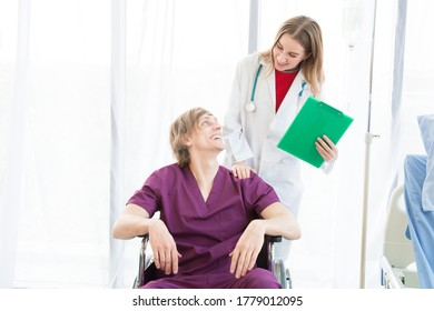 The male patient wearing in a patient dress in a wheelchair and female beautiful doctor is wearing a doctor uniform have a stethoscope and holding a green paper standing on the side.