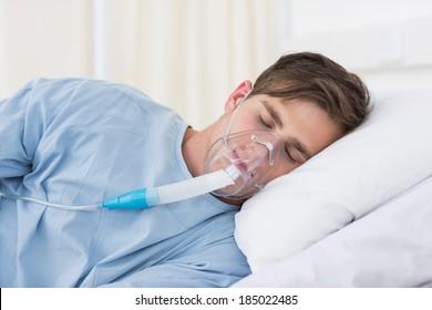 Male patient wearing oxygen mask lying on hospital bed