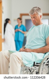 Male patient in a wheelchair next to nurses in hospital