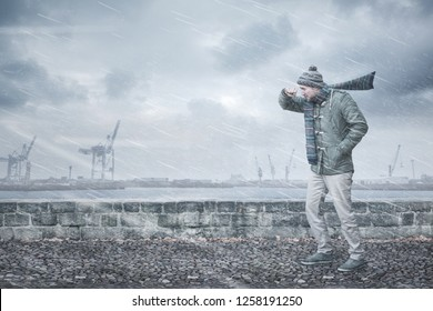 Male pedestrian is facing strong wind and rain