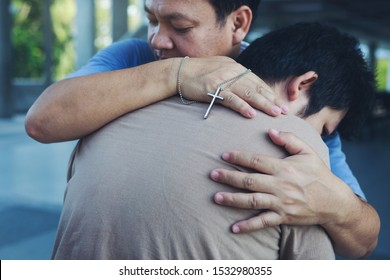 Male people christian adult health care hug to friend team support and encourage anointed believe with cross crucifix in hand