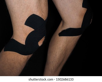 Male person with black supporting tape on knees at close-up isolated towards black