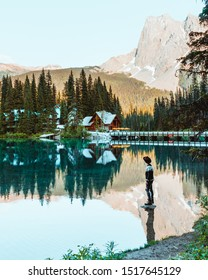 Male person with a hat standing on a rock in a lake with turquoise water (Emerald Lake in Yoho National Park in Canada). In the background there are cozy wooden cabins and lake lodges in the forest.