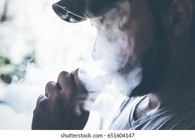 male person holding an ecig and vaping