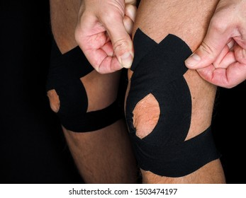 Male person with knee injury, fitting support tape around kneecap, at close-up isolated on black