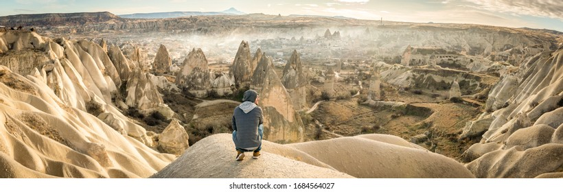 Male person low on his knees looking over the dramatic valley with Goreme town in the background. Solo exploration in Turkey. Cinematic Travel destination-Cappadocia 2020.