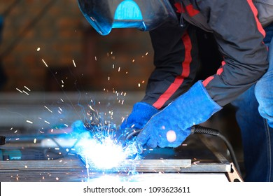 Male person in mask welding metall construction, blue welding arc. Concept of manufactory.