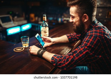 Male person with phone sitting at the bar counter