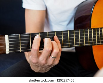 Male person playing classical guitar unplugged at closeup