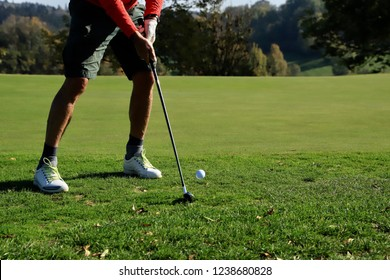 Male person playing golf. Partial view of the legs in short sportive trousers, sport shoes, socks and bare calves. Golf club on the grass, ball in the air. Moment after hitting the ball. Sunny day.