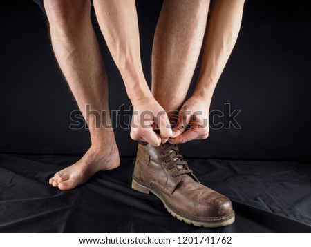Male person putting on leathery boots, no clothes, on black velvet towards black