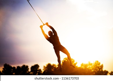 male person silhouette flying in sky, silhouette man flying on a rope, human  male gymnast hanging on rope against the background of clouds and sunset