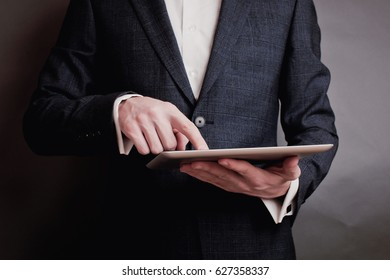 male person using a digital tablet man's hand typing text message zooming digital image on touchpad businessman using his wireless devices during a meeting work on a tablet screen