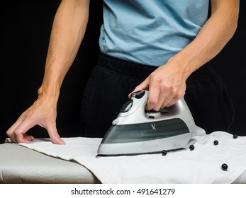 Male person using a steaming hot iron, on a white shirt
