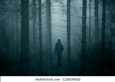 Male person walking alone in snowy misty forest fairytale. Double exposure used.