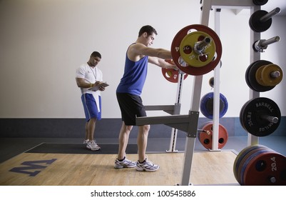 Male personal trainer with male client lifting weights