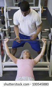 Male personal trainer with female client lifting weights