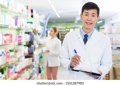 Male pharmacist is attentively stocktaking medicines with notebook near shelves in pharmacy