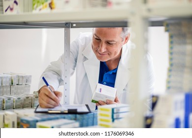 Male pharmacist checking medicines inventory at hospital pharmacy. Pharmacist in drugstore or pharmacy taking notes. Portrait of health care doctor in pharmacy writing on clipboard