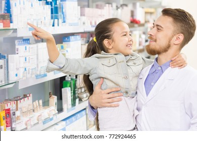 Male pharmacist holding young girl talking to her cheerfully while she is pointing at the medications on the shelf children childhood care health professionalism friendly chemist pharmacy medical
