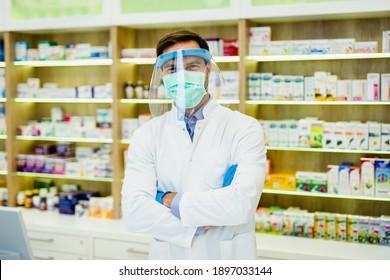 Männlicher Apotheker mit Schutzmaske und Gesichtsschild auf seinem Gesicht, arbeitet in der Apotheke. Konzept der medizinischen Versorgung.