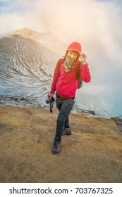 Male photographer with backpack standing on top of a mountain and enjoying sunrise, Colorful Kawah Ijen volcano crater lake