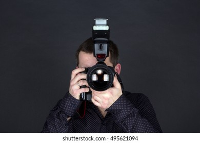 male photographer with camera and flash