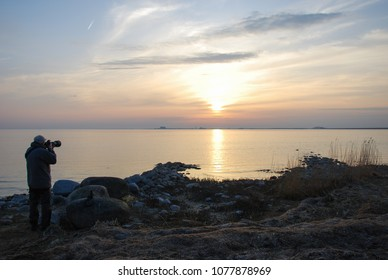 Male photographer capturing a beautiful sunset by the sea