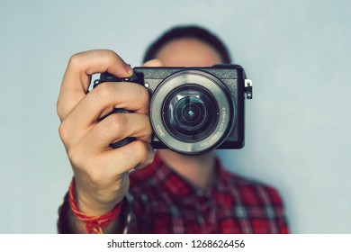 male photographer hold camera in his hands. Mirrorless camera close up in the hand of a young man on a blue background. The reporter's taking a picture. the photographer looks into the camera.