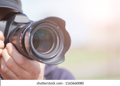 male photographer with a large professional camera looks into the viewfinder and takes pictures, toned