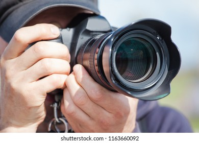 male photographer with a large professional camera looks into the viewfinder and takes pictures