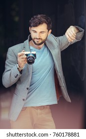 Male photographer looking on screen of camera. Portrait of handsome man outdoors