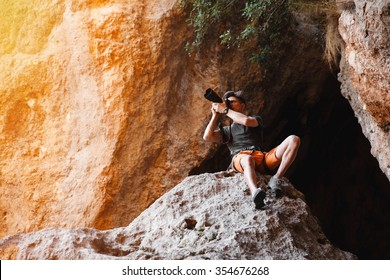 Male photographer on the cliff in the cage shooting on dslr camera. Concept of freelance working - stock image